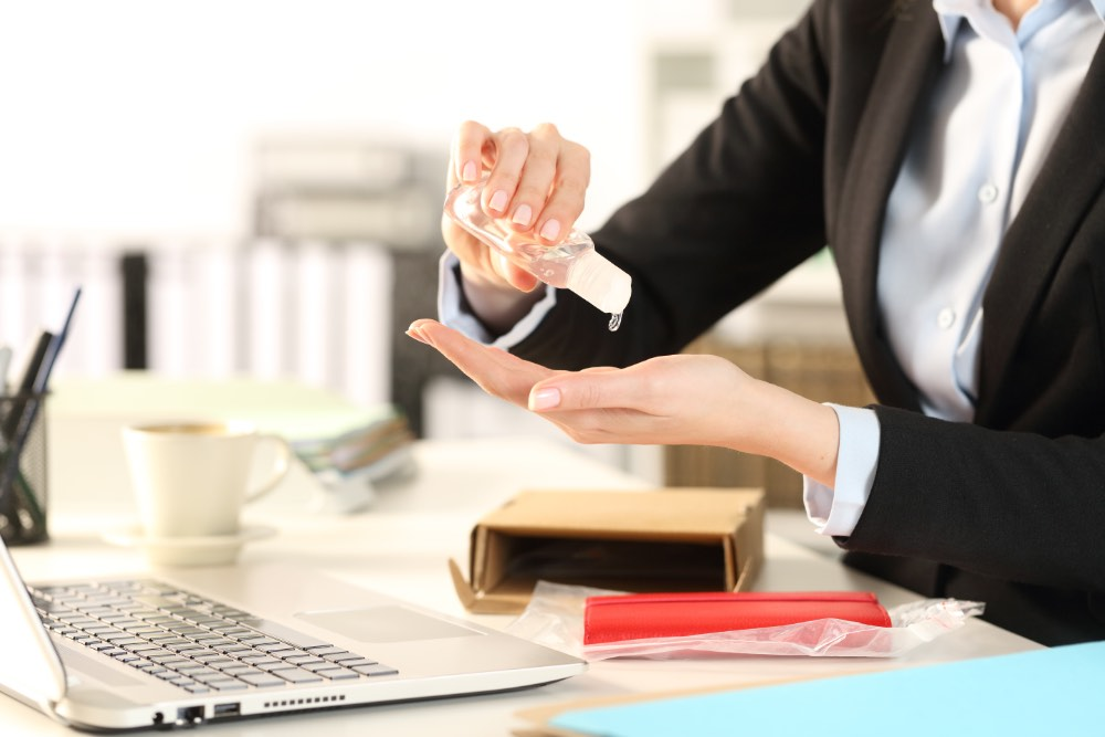 Woman sitting at desk using hand sanitizer.