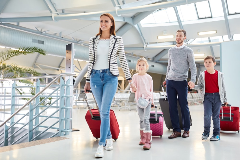 Family of four pulling luggage through airport.