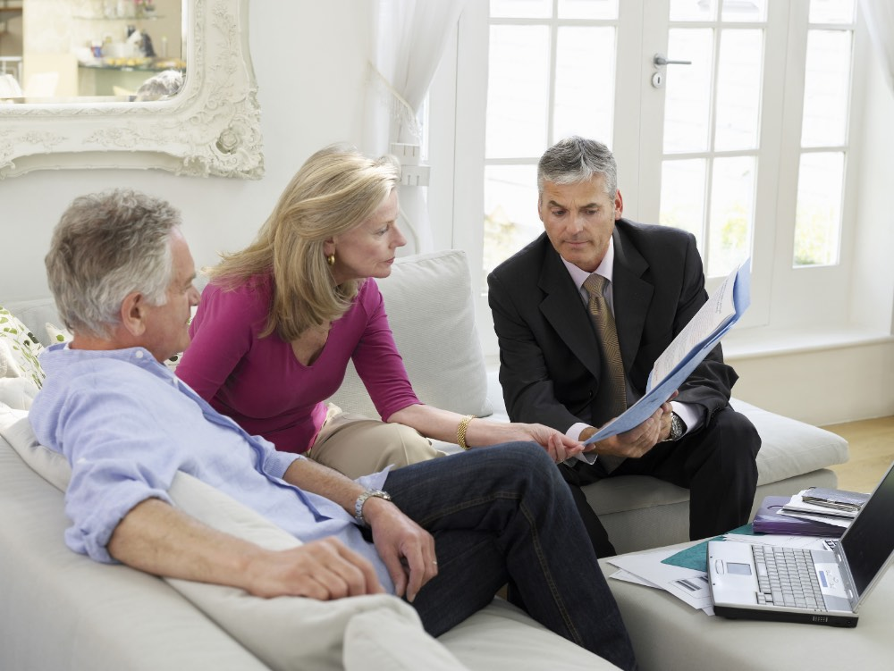 A couple sitting on couch reviewing documents with an advisor.